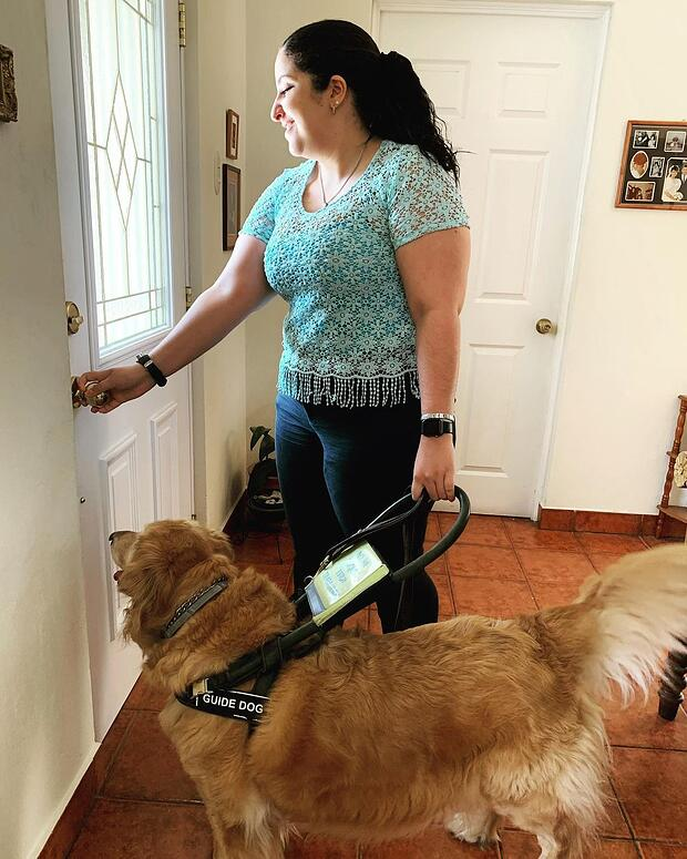 Marcela is in front of the door, holding the doorknob with the right hand with the Sunuband on her wrist and with her left hand she is holding her guide dog's harness. Her guide dog, Fitgy, is a golden retriever.